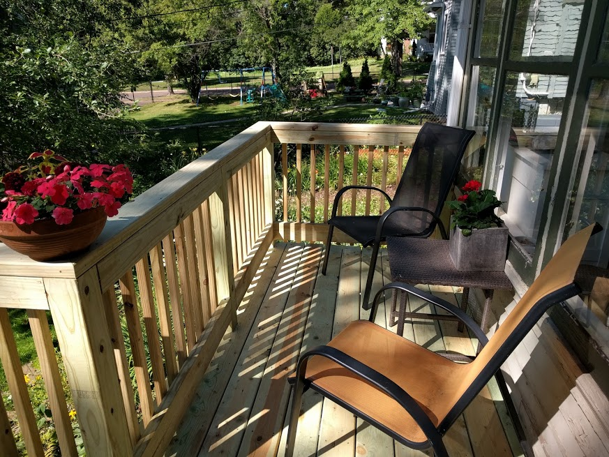 While we were in Europe, some nice construction guys made our home equity loan worthwhile when they tore down our jinky staircase and built a new one, also adding in a wee deck. So now, as summer reaches its end, we take coffee and books out to these chairs. Setting a spell, we lean our heads back, watch the squirrels scrabbling high in a tree, and marvel at our great good fortune.